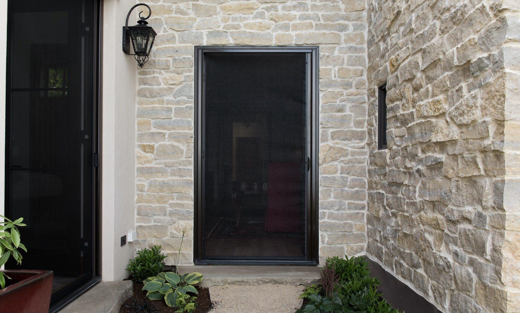 genius retractable screen door in front of stone